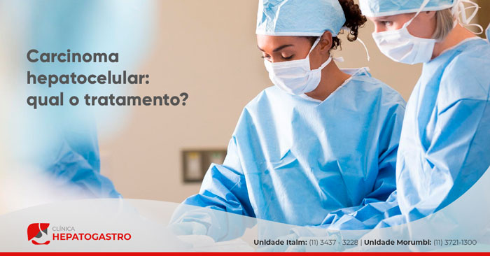 Ao fundo da imagem, há duas doutoras de máscara e roupas para um tratamento cirúrgico.